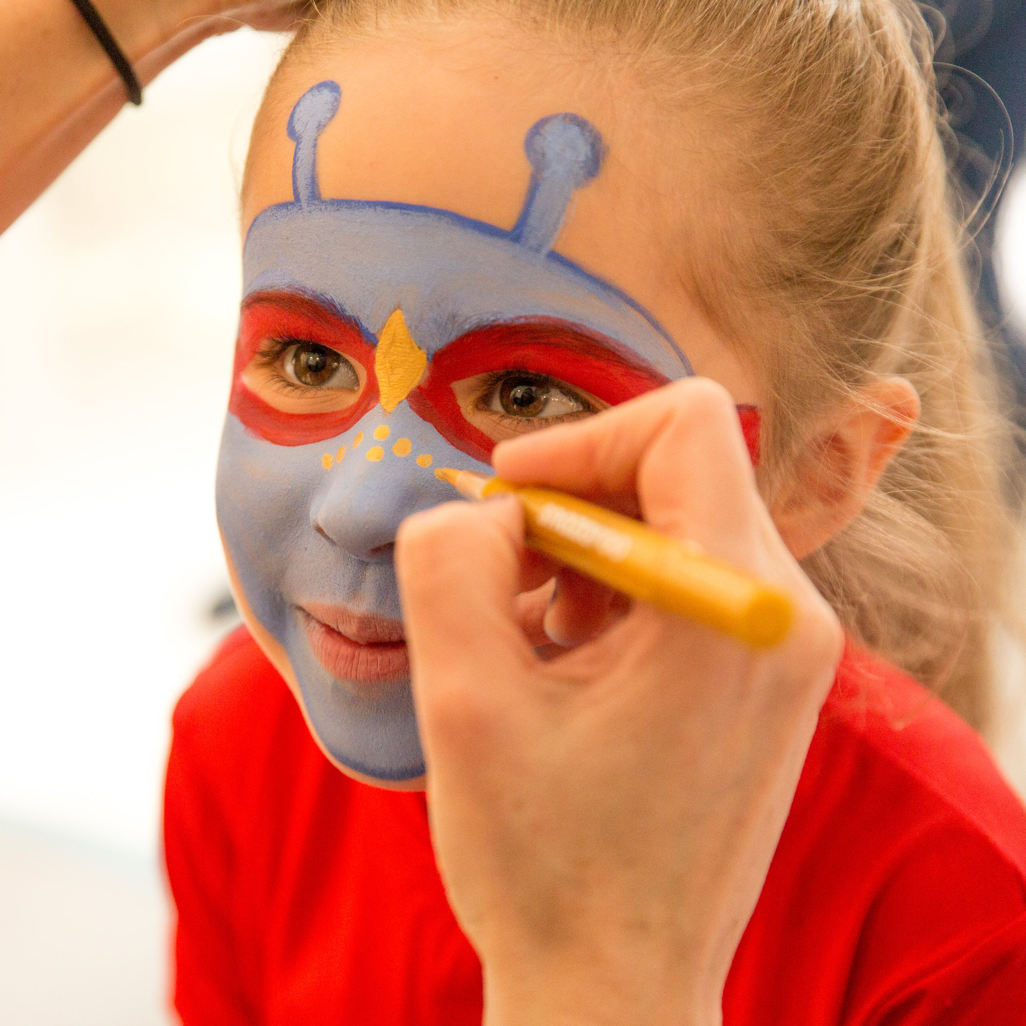 Child getting face painted as an Alien Hero