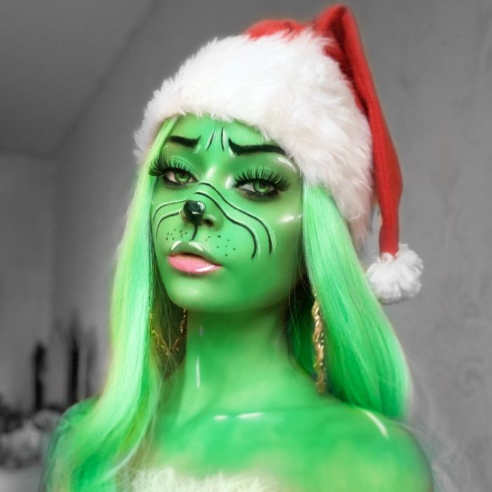 girl with Grinch Christmas face paint design