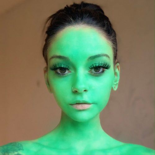 girl with step 1 of Grinch Christmas face paint design
