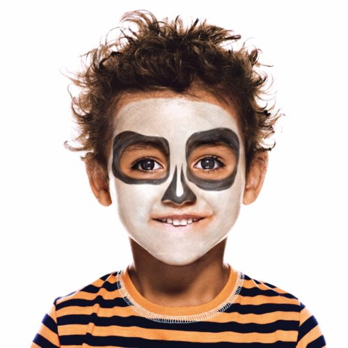 Boy with step 2 of Cheeky Skeleton Halloween face paint design