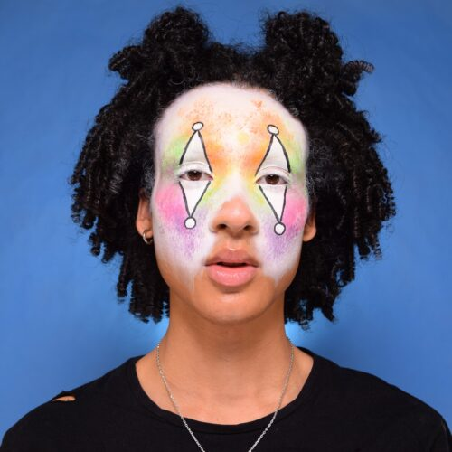 Boy with step 2 of Sparkle Clown face paint design for Halloween