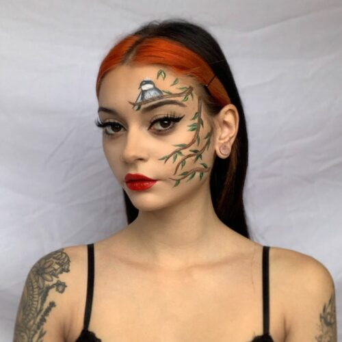 Woman with step 2 of a Christmas holly branch face paint look
