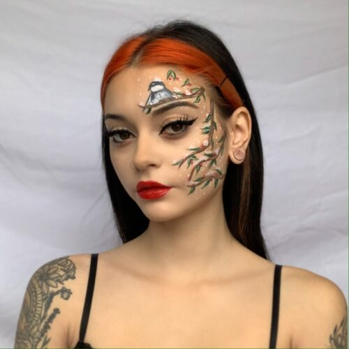 Woman with step 3 of a Christmas holly branch face paint look